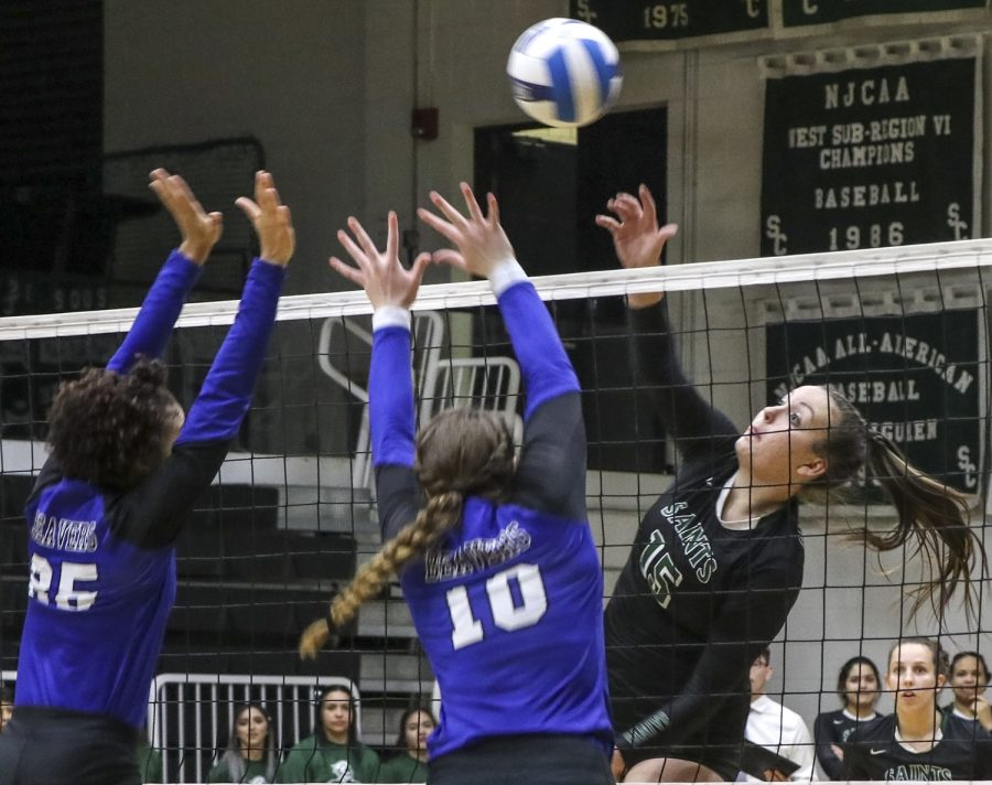 Thais+Vieira+hits+into+two+Pratt+defenders.+The+sophomore+middle+blocker+had+four+kills+on+the+night.+The+Lady+Saints+easily+won+the+match+in+three+straight+sets.