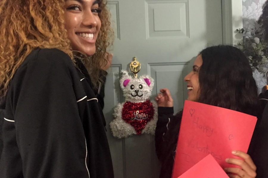 Basketball players Destiny Alston and Kamry Perez knock on the door of a senior citizen to give them a Valentine. This is the second time the library has sponsored this event.
