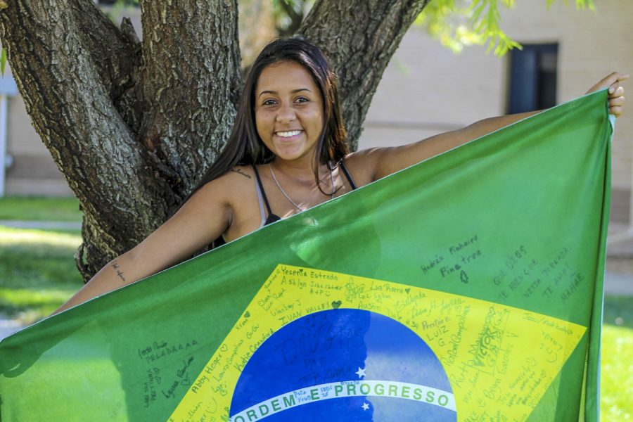 Victoria Martins, a Freshman majoring in biology, proudly holds up the flag of her home country, Brazil, as she poses for a picture. Signatures paint the flag from her friends in America and from her hometown of Sete Lagoas.