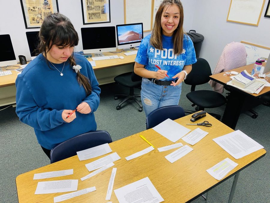 Annette Meza, managing editor, helps Denis Perez, a new reporter, put her story in order. The two cut her notes apart and put the story together as if it were a puzzle.
