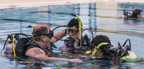 Instructor Mike Hale is showing high school students what to do when his oxygen tank runs out of oxygen. As students are practicing underwater, Hale turns off a student's tank to give a step-by-step safety process.