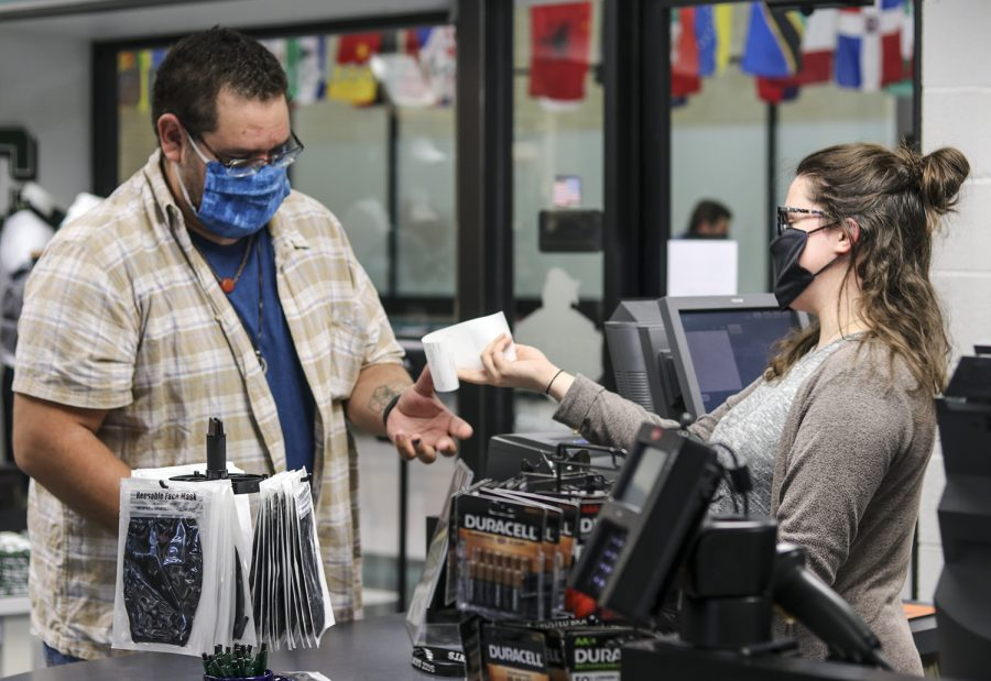 Matt Maturey, help desk support, buys a new Saints mask from Madelyn Sander, bookstore associate. The Saints bookstore ordered masks with the school mascot so staff, faculty and students can show off their school spirit.
