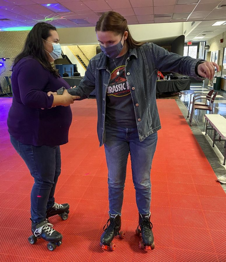 Holding on tight, freshmen Destiny Vasquez and Krisi Anderson try not to fall during their first attempt at skating in the student union. The freshmen eventually mastered it and rolled around but they say it was after a lot of falling and scrambling.