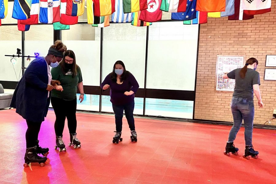 Students help each other across the hard plastic roller rink floor. The student union was transformed from the normal hangout spot, Feb. 22, to a skating rink.