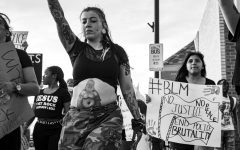 A protesters holds their signs while marching peacefully down Kansas Ave. The March was done in order to support the Black Lives Matter Movement that was sparked after the death of Trayvon Martin in 2012.