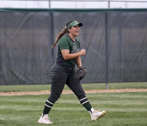Jacie Scott, left fielder, cheers as her teammate and pitcher, Ireland Caro, gets the last strikeout of the inning. This pitch gave the Lady Saints an 8-6 win for game two of the doubleheader against Garden City.