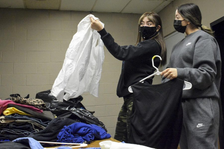 Elisa Bolanos, business management major, and Hannah Rosales, business administration major, sort through donated clothes in the back of the store. The two PBL club members try to create outfits that might go together and appear professional.