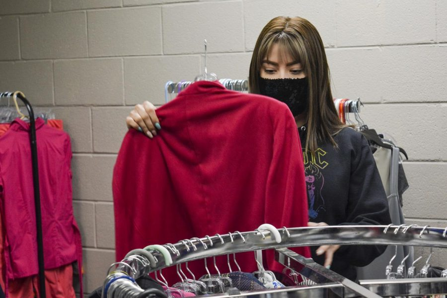 Elisa Bolanos, business management major, combs through clothes on racks to get ready for the grand re-opening of the E-boutique on April 15 at 12:30 p.m. The Phi Beta Lambda club sponsors the clothing store to offer free clothes for students and community members.