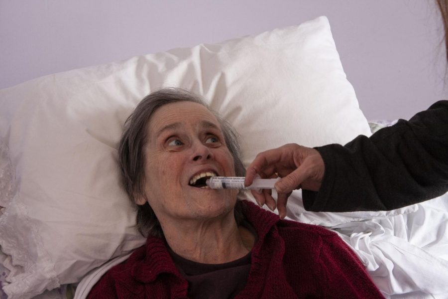 """Anne McKeown receives her daily medication. Jean Fields, McKeown's daughter and caregiver, uses a syringe to break down daily medications for easy administration. Fields said she learned this technique from a nurse. Fields added, """"It has been a big help because she doesn't like to take her medicine, and this is an excellent way for me to not get bit""""."""