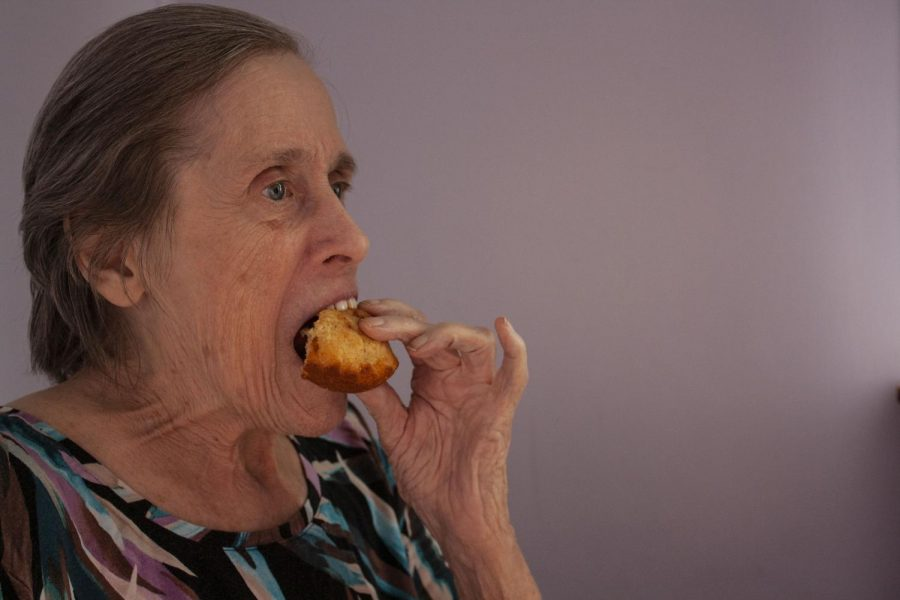 """Anne McKeown eats a cornbread muffin. Her daughter, Jean Fields, said McKeown rarely passes up cornbread and sometimes """"I have to move the plate out of her reach, or she'll eat them all."""" Dementia has not, for the most part, diminished McKeown's appetite or ability to feed herself, according to Fields."""