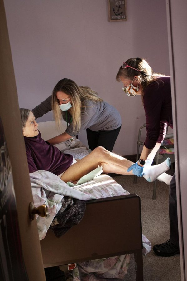 Physical therapists Dawn Lombardi (right) and Susan Mann (left) help Anne McKeown (center) get into bed after a physical therapy session. McKeown is recovering from partial hip replacement after a recent hip fracture. In order avoid recovery time in a rehabilitation center, McKeown receives physical therapy sessions twice a week in her home.