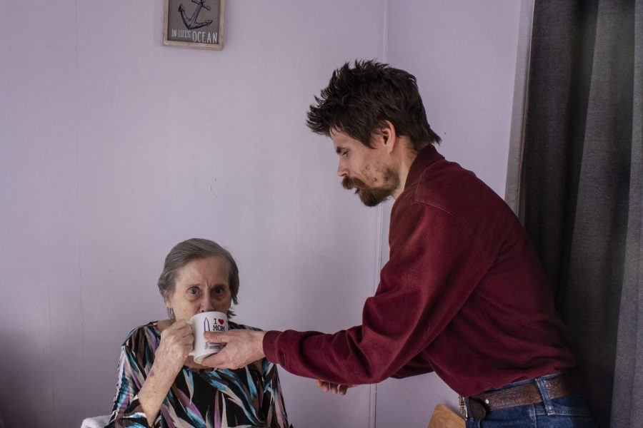 """David McKeown helps his mother, Anne McKeown, to steady her hands while drinking a cup of hot chocolate. He frequently assists in caring for his mother because """"We're family and we help each other""""."""