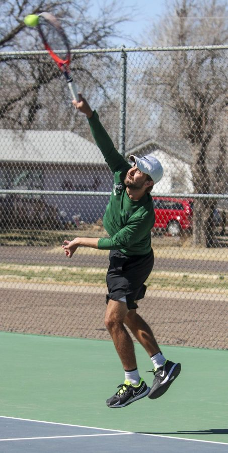 Luciano Fisicaro comes down on a serve during a home match in Blue Bonnet Park in Liberal. The freshman from Argentina is ranked No. 4 in the nation for singles and No. 6 for doubles play.