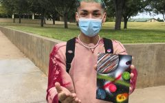 Adrian Mendoza, sophomore accounting major, shows off his spray paint art. It took three minutes for this solar system to be painted.