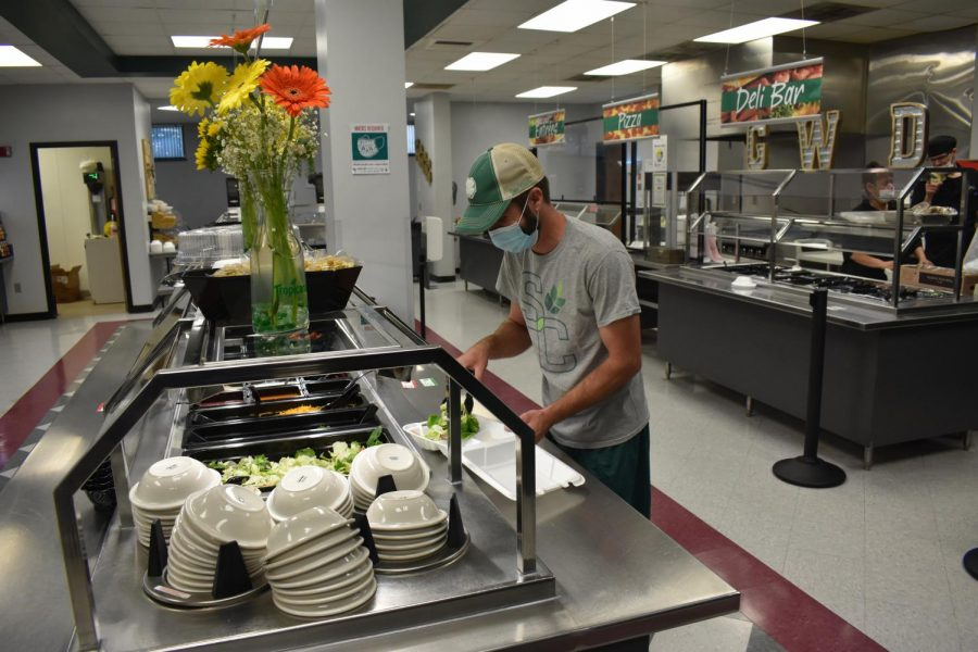 Staff personnel Paul Fisher making a salad with the newly open salad bar.