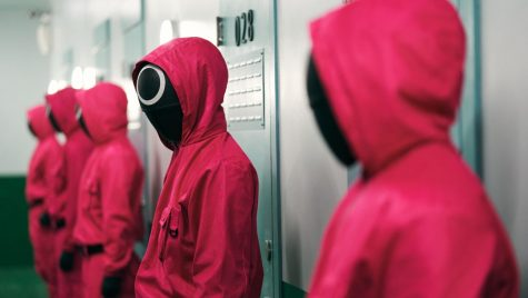 Mysterious red-hooded figures line up against a series of doors.